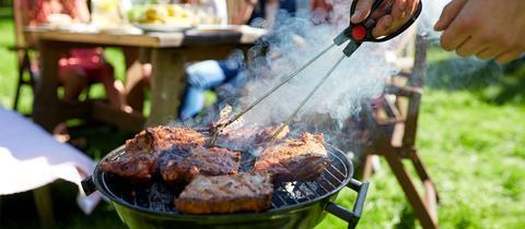 Ein Mann wendet Fleisch auf dem Grill.