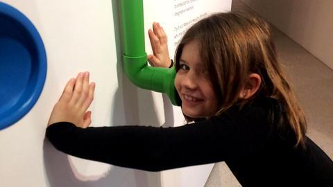 Eva-Lotte steht mit den Händen an einer Infotafel gelehnt in der Grimmwelt in Kassel.