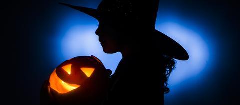 Ein als Hexe verkleidetes Mädchen trägt einen Kürbis