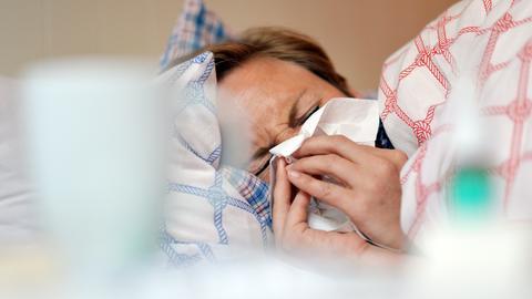 Mann mit Erkältung im Bett