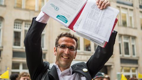 Fahrrad-Aktivist Heinrich Strößenreuther hält die gesammelten Unterschriften für seine Initiative Volksentscheid Fahrrad in die Höhe