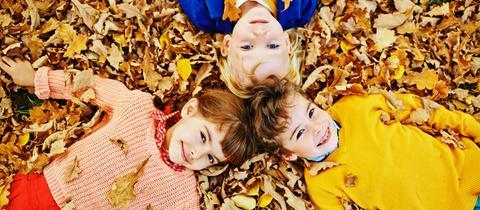 Kinder liegen im Herbstlaub