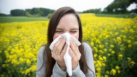 Eine junge Frau hält sich mit zugekniffenen Augen ein Taschentuch vor die Nase, während sie vor einem Rapsfeld steht.