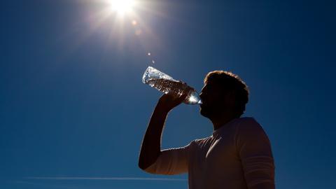 Mann trinkt Wasser in der Sommerhitze