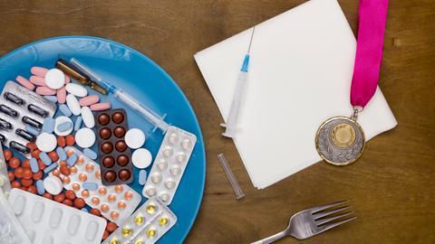 Tabletten und Medaillen als Symbolbild für Doping