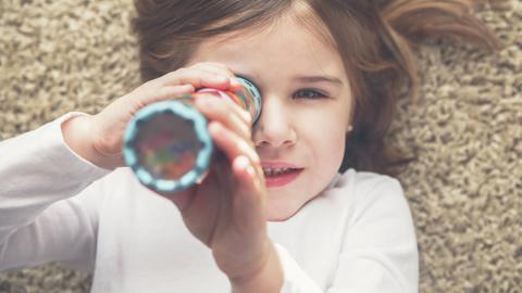 Ein Mädchen schaut durch ein  Kaleidoskop