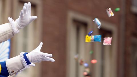 Karnevalisten werfen beim Rosenmontagsumzug Süßigkeiten.