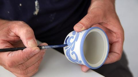 Ein Mann bemalt einen Keramik-Topf
