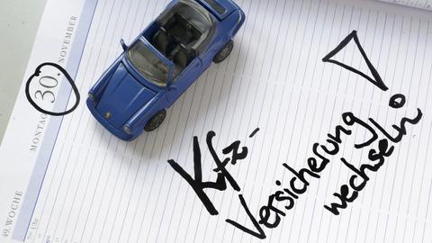 Ein Modelauto steht auf einem Kalenderblatt vom 30. November, der Stichtag für einen Wechsel der Kfz-Versicherung.