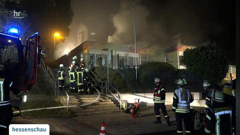 Feuerwehrmänner stehen vor dem brennenden Kindergarten in Neckarsteinach