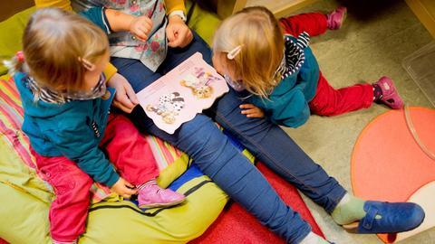 Eine Erzieherin liest mit Zwillingen ein Buch in der Kita, die bis zu sechs Stunden kostenfrei ist.