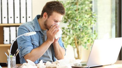 Ein Mann sitzt stark erkältet an seinem Arbeitsplatz