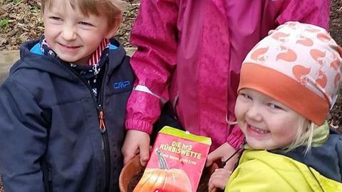 """Kinder aus dem Waldkindergarten """"Die Wühlmäuse"""" in Rodgau halten einen Blumentopf mit Kürbiskernen."""