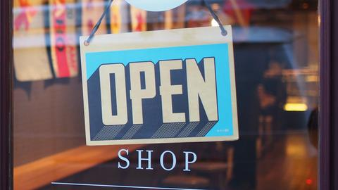 """""""Open""""-Schild hängt an einer Ladentür"""