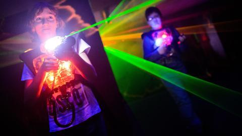 Ein Junge zielt beim Laser-Tag mit einem Phaser auf andere Mitspieler.