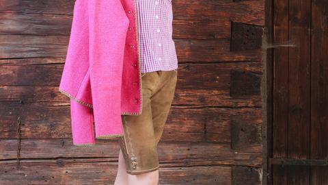 Eine Frau trägt eine knielange Lederhose mit rotweiß karierter Bluse und einer rosa Trachtenjacke.
