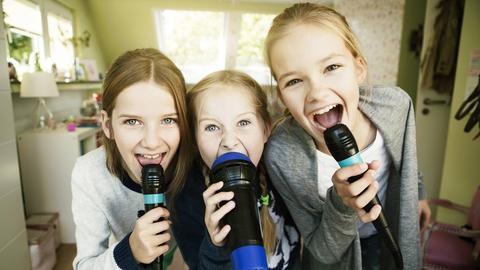 Drei Mädchen singen ins Mikrofon.