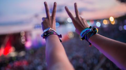 Eine Besucherin des Melt! Festivals hält vor der Main Stage ihre Arme in die Höhe und zeigt das Victory-Zeichen.