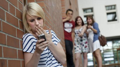 Mädchen wird von einer Gruppe Jugendlicher gemobbt