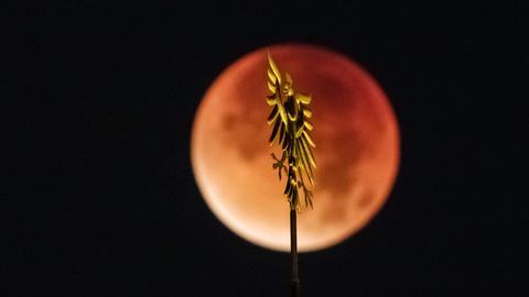 Der rot erscheinende Vollmond steht während einer totalen Mondfinsternis hinter dem goldenen Adler aus dem Frankfurter Stadtwappen, der auf dem historischen Rathaus der Stadt, dem Römer, prangt.