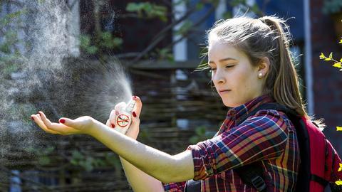 Mädchen sprüht sich mit Mückenspray ein
