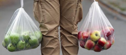 Ein Mann trägt zwei Plastiktüten mit Äpfeln
