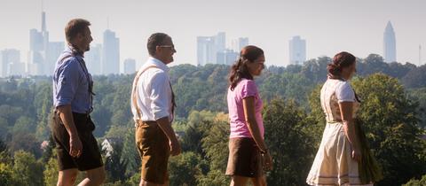 Vier Besucher in Tracht gehen auf das Oktoberfest auf dem Lohrberg in Frankfurt