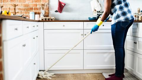 Eine Person putzt mit einem Wischmob den Boden in der Küche