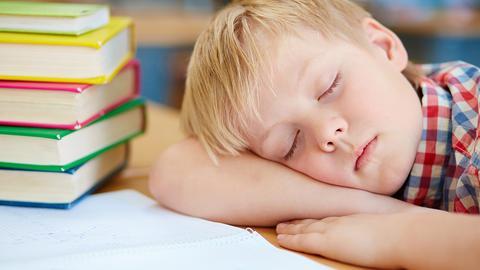 Junge liegt schlafend neben einem Stapel Bücher