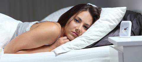 Eine Frau liegt in ihrem Bett und kann nicht schlafen