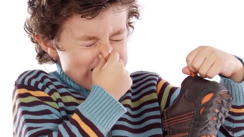 Ein Junge hält sich die Nase zu und hat seine stinkenden Schuhe in der Hand.