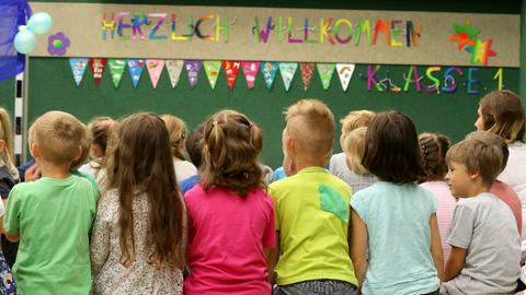 Erstklässler sitzen in einem Klassenraum und werden empfangen.