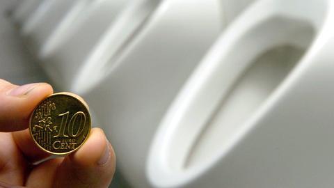 Ein Schüler hält auf einer Toilette vor einer Reihe von Pissoirs ein 10-Cent-Stück in der Hand.