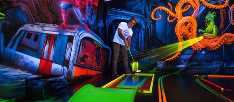 Ein Mann spielt Indoor-Minigolf auf einer neon-leuchtenden Bahn mit Fanatasie-Motiv im Hintergrund