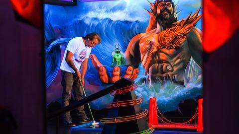Ein Mann spielt Minigolf auf einer neon-leuchtenden Bahn