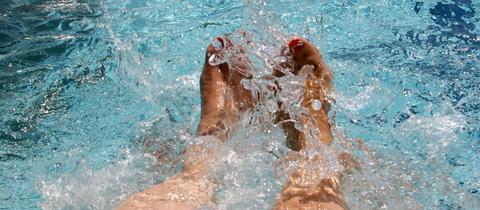 Füße im Schwimmbad-Wasser