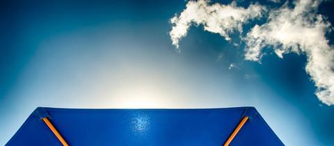 Ein blauer Sonnenschirm mit Blick in den Sommerhimmel