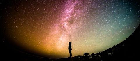 Sternegucker betrachtet einen bunt schillernden Sternenhimmel
