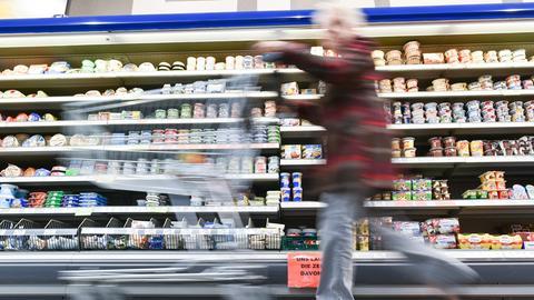 Eine Kundin schiebt ihren Einkaufswagen an einem Kühlregal vorbei.