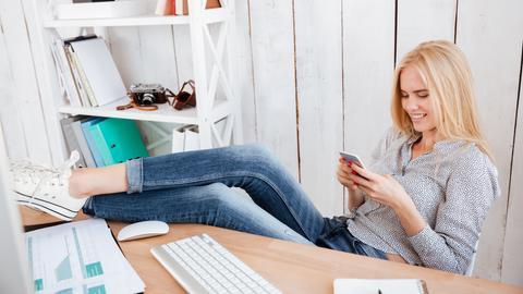 Eine Frau hat die Beine auf den Schreibtisch hochgelegt und schaut in ihr Handy