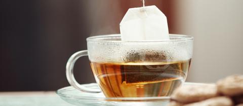 Ein Teebeutel hängt in einer Glastasse.