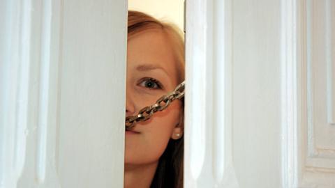 Frau öffnet Tür, die mit einer Türkette gesichert ist