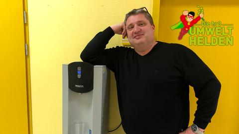 hr3 Umweltheld Andreas steht an dem Wasserspender in seiner Schule