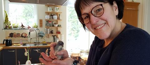 Umweltheldin Anja hält einen kleinen Vogel in der Hand
