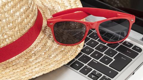 Sonnenhut und Sonnenbrille liegen auf einem Laptop