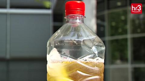 Plastikflasche gefüllt mit Apfelsaft und Eis