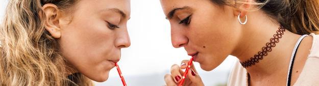 Frauen trinken aus einem Pappbecher