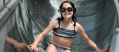 Ein Mädchen rutscht die Wasserrutsche im Waldschwimmbad Melsungen