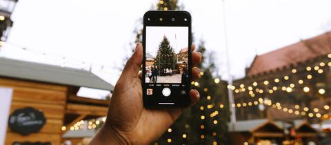 Ein Mann fotografiert Besucher auf einem Weihnachtsmarkt
