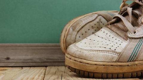 Weiße Turnschuhe auf einem Holzboden